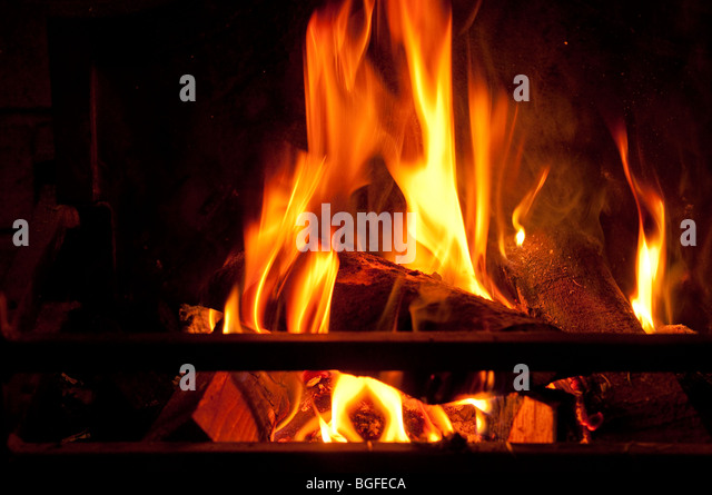 A log and coal fire burning fiercely - burning carbon / fossil fuels. - Stock Image