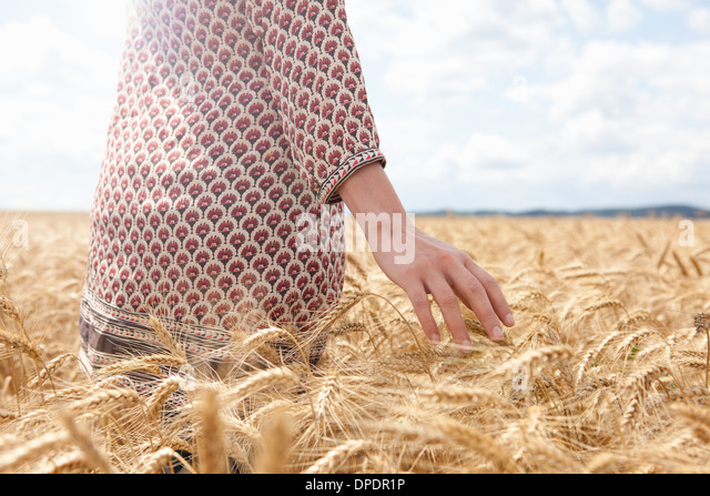 Mid section of woman in wheat field - Stock Image