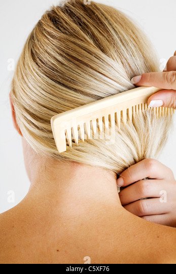 woman combing hair - Stock Image