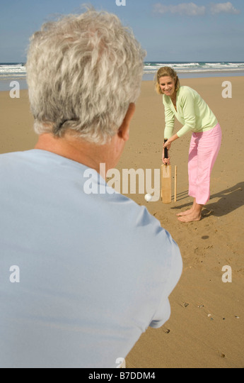Couple playing cricket on a beach - Stock Image