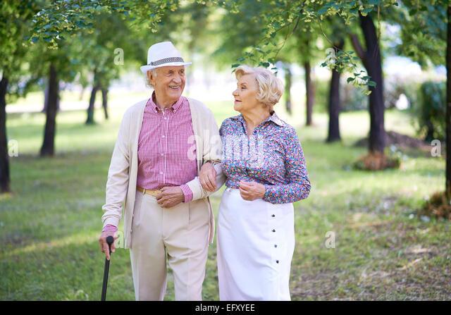 Elegant seniors taking a walk in the park in summer - Stock Image