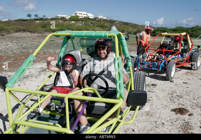 Grand Turk Cockburn Town dune buggy excursion tour father son helmets - Stock Image
