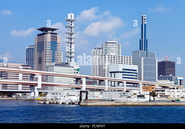 Waterfront cityscape of sea port city of Kobe Japan in Hyogo Prefecture with flyover bridge, office buildings and - Stock Image