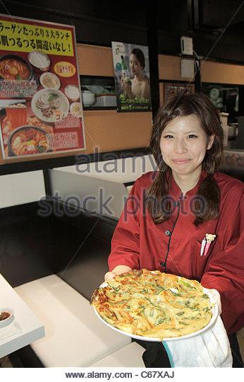 Japan Tokyo Ikebukuro restaurant interior Asian woman waitress serving pizza plate kanji hiragana characters - Stock Image