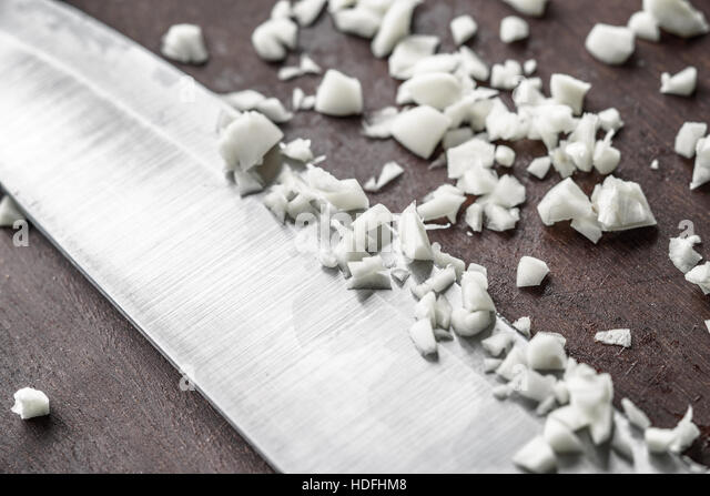 Chopped onion with knife on the wooden board - Stock Image