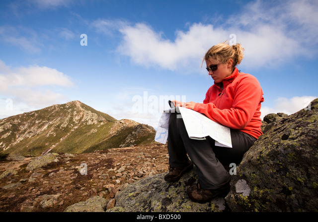 A female hiker checks her location by using a map and compass. - Stock Image