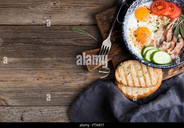 Breakfast set. Pan of fried eggs with bacon, fresh tomato, cucumber, sage and bread on rustic serving board over - Stock Image