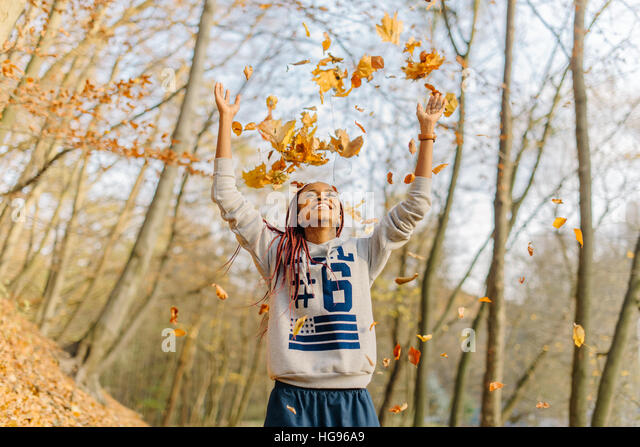 african girl playing with bunch of leaves, enjoying warm autumn day in park. Have fun in autumn - Stock Image