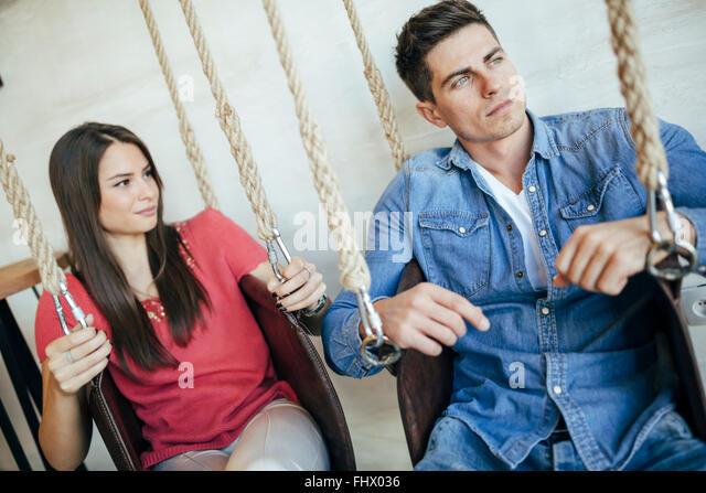 Portrait of couple sitting in swings posing - Stock Image