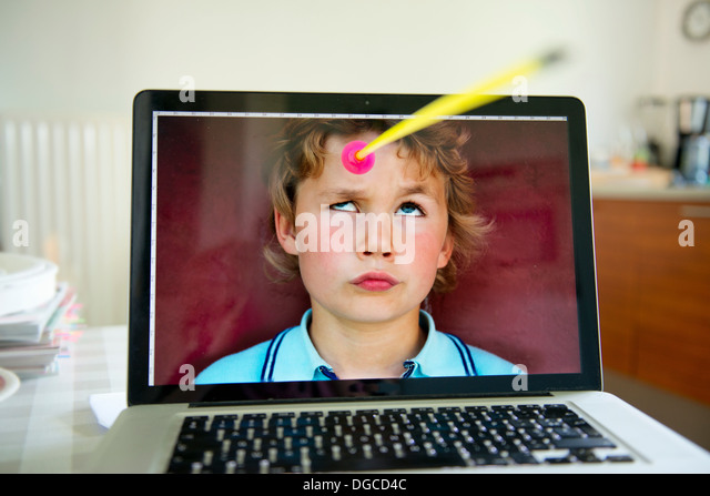 Boy looking up from laptop screen at toy arrow - Stock-Bilder
