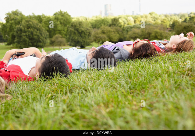 Teenagers lying in a park - Stock Image