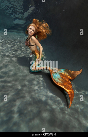 Young blond mermaid at the bottom of a pool in Virginia Beach, Virginia - Stock Image