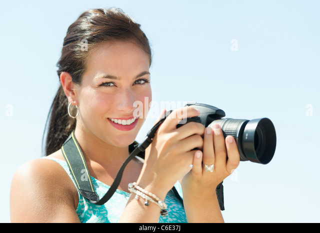 USA, New Jersey, Jersey City, Portrait of young woman taking pictures with camera - Stock Image