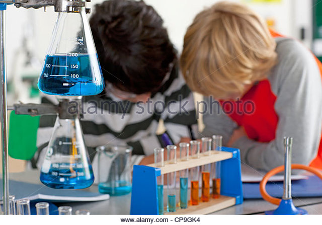 Students performing experiment in school chemistry laboratory - Stock Image