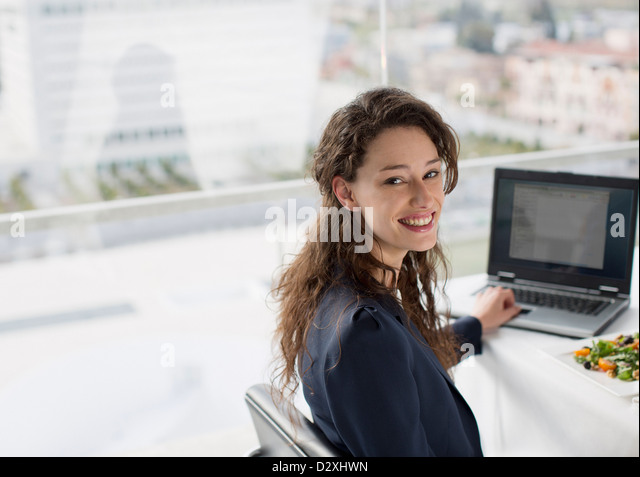 Portrait of smiling businesswoman using laptop and eating lunch - Stock Image
