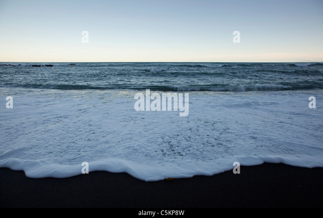 Waves lapping on black sand at dusk, Owhiro Bay, Wellington, New Zealand - Stock Image