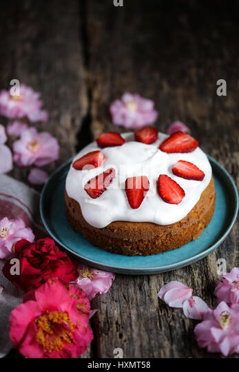 Cardamom cake with cream cheese frosting and fresh strawberry - Stock Image