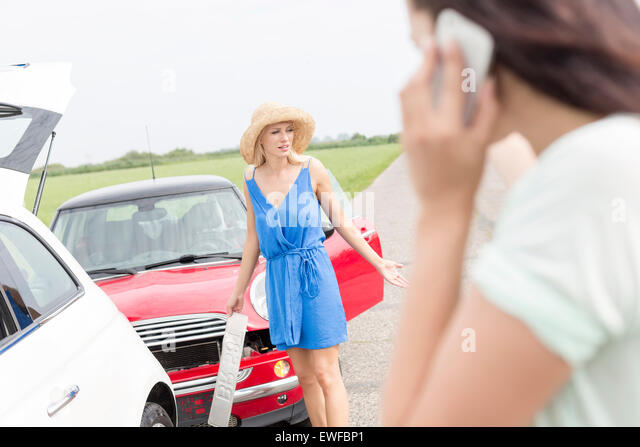 Angry woman standing by damaged cars with female using cell phone in foreground - Stock Image
