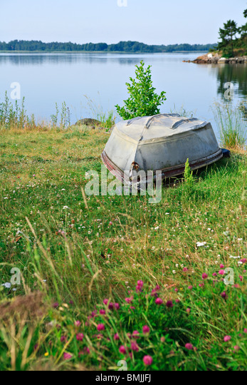 Stranded boat by lake - Stock Image