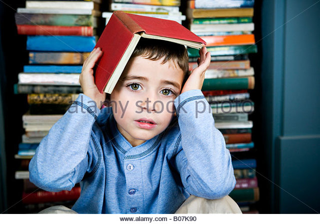 little boy with book on his head - Stock Image