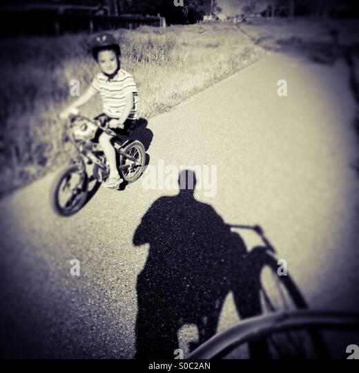 A seven year old boy rides his bike by a man on a bike path. - Stock Image