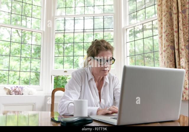 Mature woman working on laptop in living room - Stock Image
