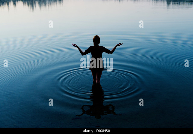 Woman meditating in peaceful lake - Stock Image