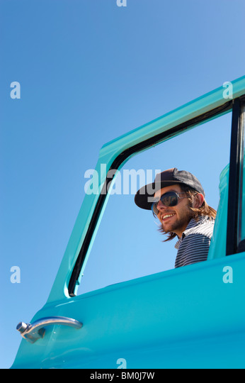 Portrait of young man through car window - Stock Image