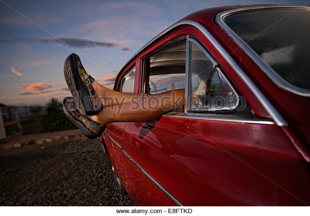 Woman's legs hanging out of car window - Stock Image