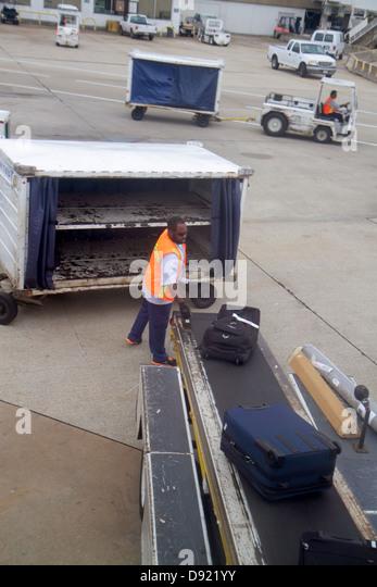 Texas Houston George Bush Intercontinental Airport IAH Black man employee baggage handler conveyor belt tarmac - Stock Image