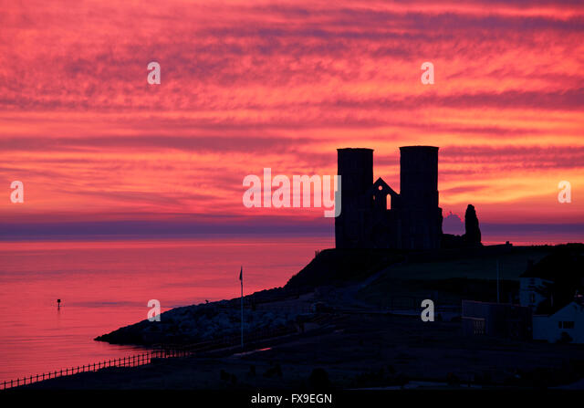Reculver, Kent, UK.13th April 2016: UK Weather. Red sky in the morning as a pre-dawn glow just before sunrise silhouettes - Stock Image