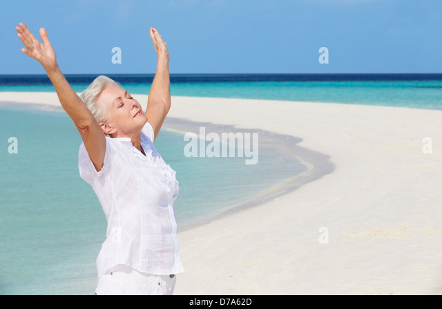 Senior Woman With Arms Outstretched On Beautiful Beach - Stock Image