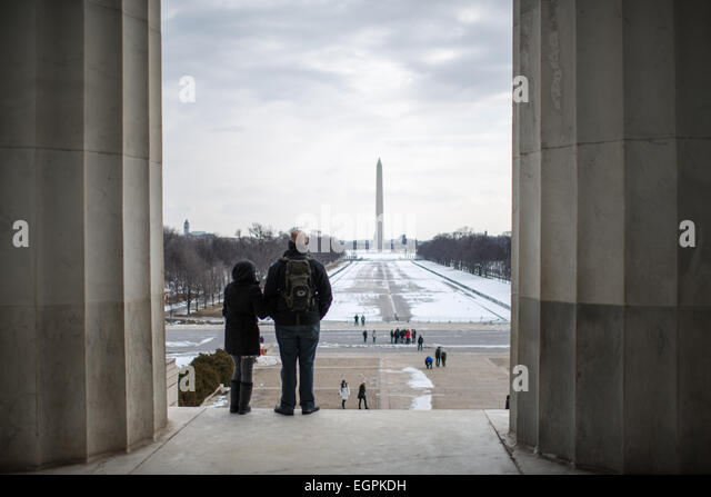 Tourists look out from the top of the steps of the Lincoln Memorial over the Reflecting Pool (drained for the winter) - Stock-Bilder