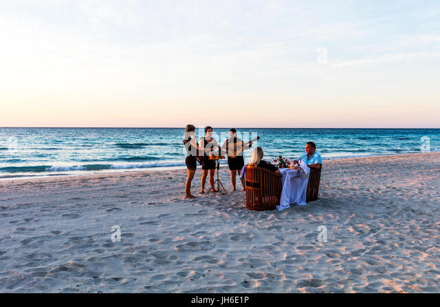 Serenade, serenaded, Serenade on beach, romantic meal, romantic meal on beach, serenading, serenading on beach, - Stock-Bilder