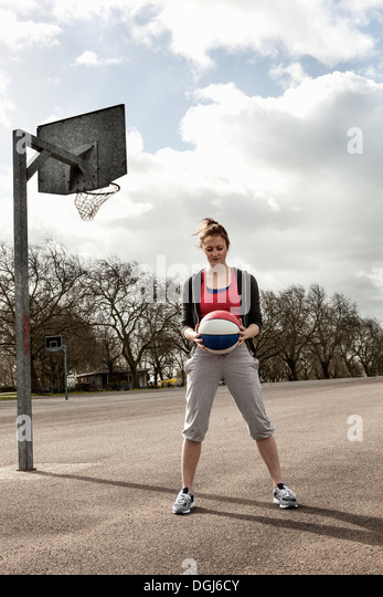 Woman holding ball at netball court - Stock Image