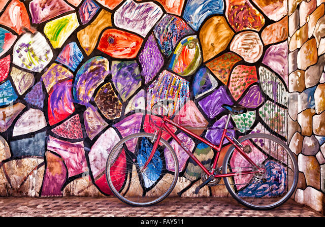 Red bicycle against colourful, abstract painted wall. - Stock Image