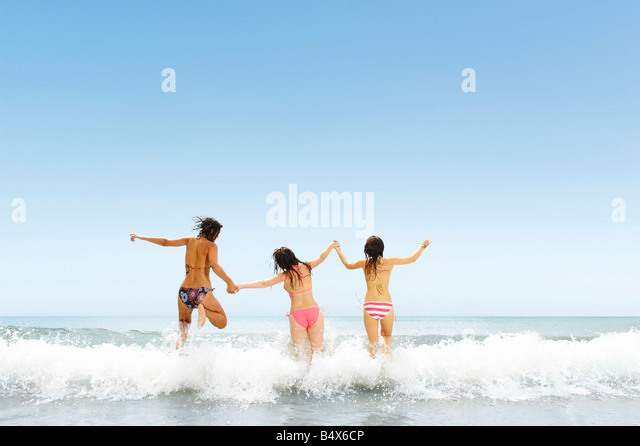 Three girls jumping over wave - Stock-Bilder