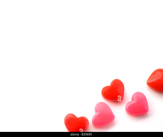 Heart-shaped candies on white background - Stock Image