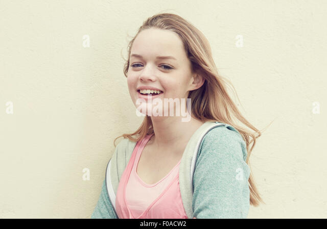 Portrait of smiling girl with long blond hair in front of wall - Stock Image