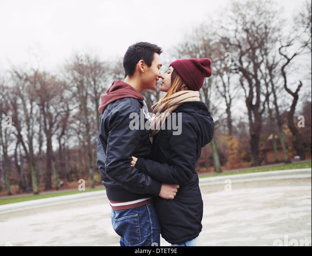 Mixed race teenage couple about to have a passionate kiss in park. Handsome young man and beautiful young woman - Stock Image