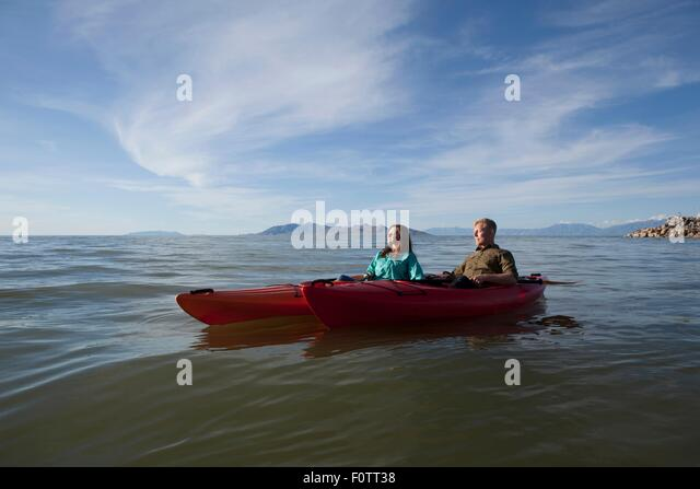 Young couple in kayaks on water, eyes closed looking away, Great Salt Lake, Utah, USA - Stock Image