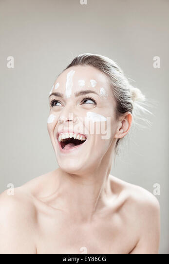 Young woman with streaks of lotion on face - Stock Image