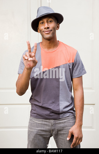 Man wearing fedora and doing peace sign - Stock-Bilder