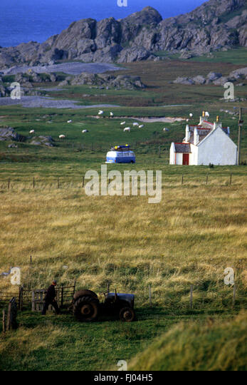 an old tractor  and farmer stands on one side of the field to a cottage and VW van with surfboards on the other - Stock-Bilder