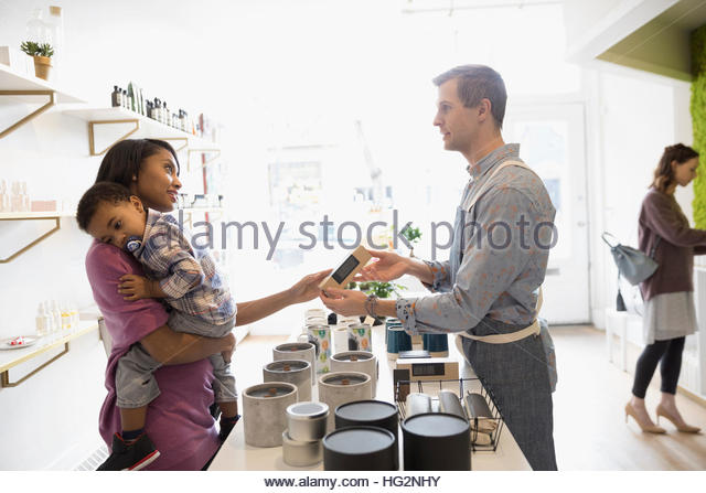 Male shop owner helping woman with son shopping for candles in home fragrances shop - Stock Image