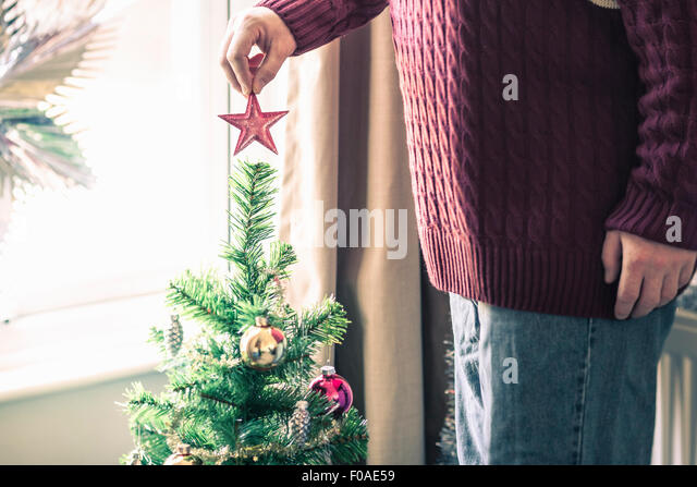 Person putting star on christmas tree - Stock Image
