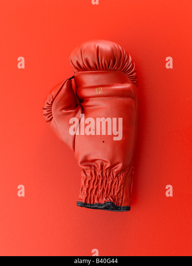 Red boxing glove on red background - Stock Image