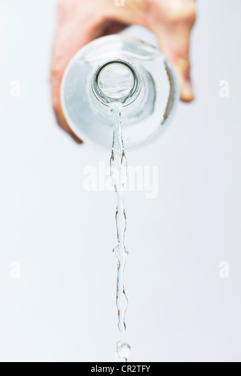 Hand pouring mineral water from a glass bottle against white background - Stock Image