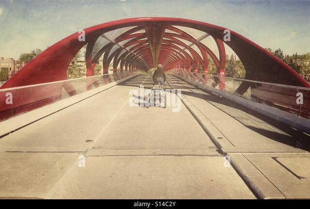 A cyclist with a bike trailer uses the designated cycle path on the Peace Bridge in Calgary, Canada. - Stock Image