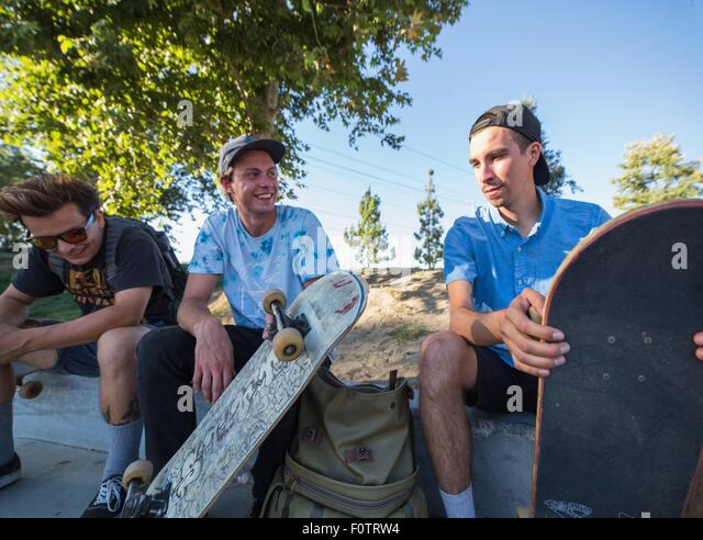 Young men with skateboards chatting in park - Stock Image